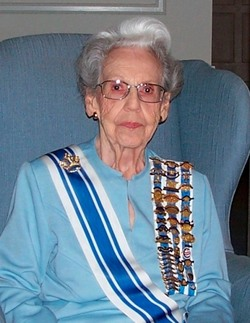 Older woman with gray hair and glasses wearing aqua-colored blouse draped with sashes