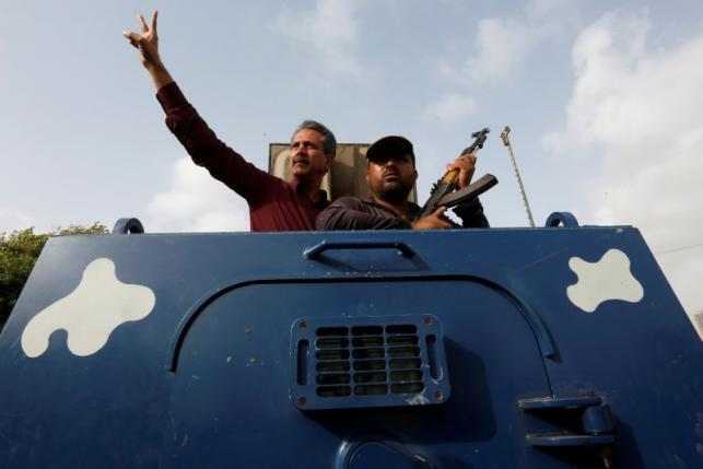 Waseem Akhtargestures from an armoured personal carrier while being taken to jail after his arrest
