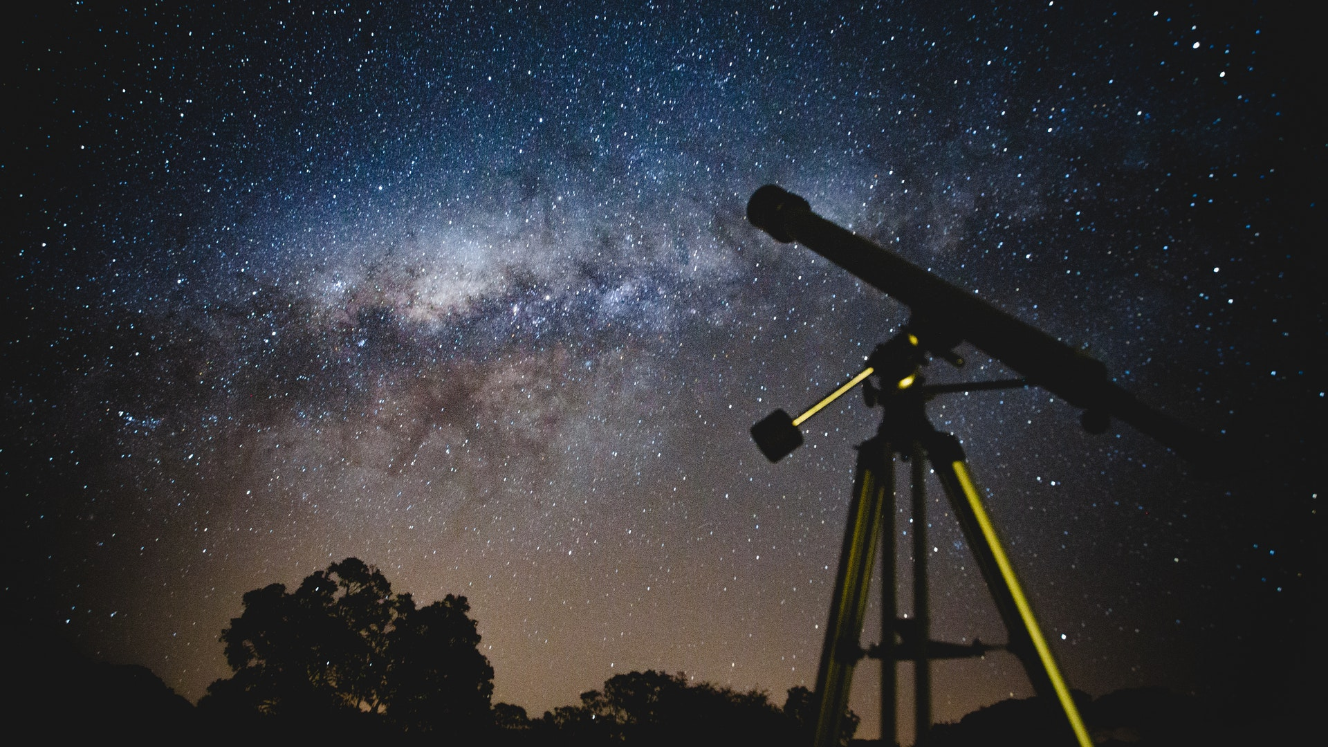 This is a picture of an unmanned telescope aimed at a clearly visible nebula in the sky. It looks just like the milky way and the sky is littered with gleaming sparkles of light emitted from the stars. This is an obvious setup of someone who is studying astrology
