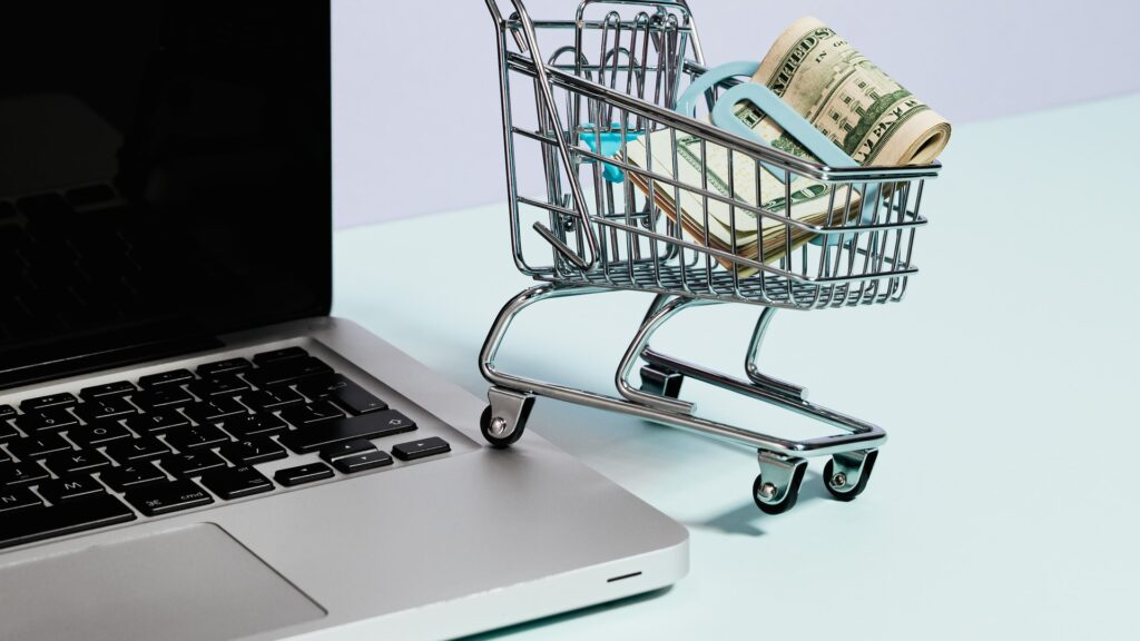 this picture contains a grey laptop with a miniature sized buggy, one leg on top of the laptop near the keyboard and the other three positioned on the table. There is also a fat wad of cash inside the buggy