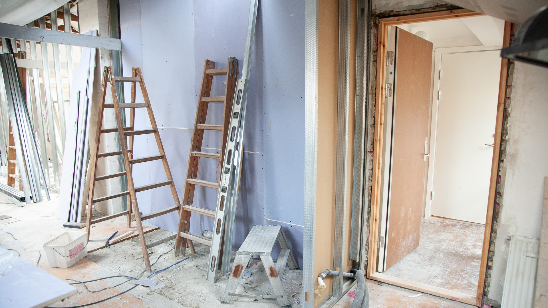 An empty room with two ladders one standing and the other leaning against the wall there are paint buckets and other construction materials littred throughout the room. the walls ahve been stripped of it's paint and it is clear that a home improvement project is underway.