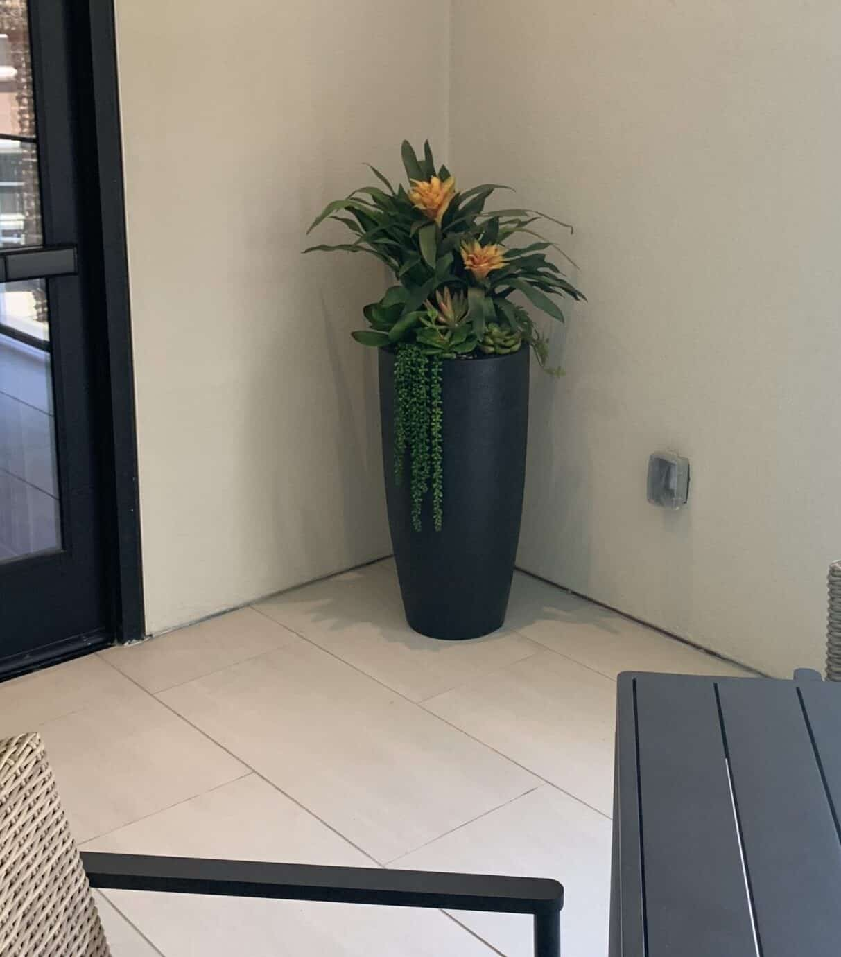 Artificial plants in a tall planter