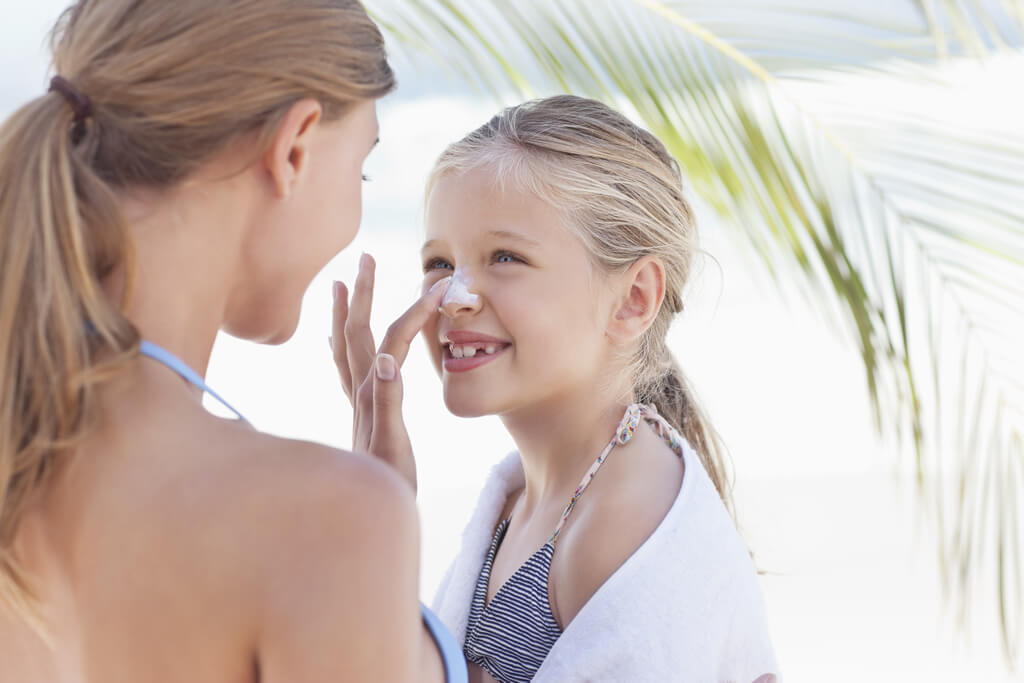 Woman applying sunscreen on daughter's nose
