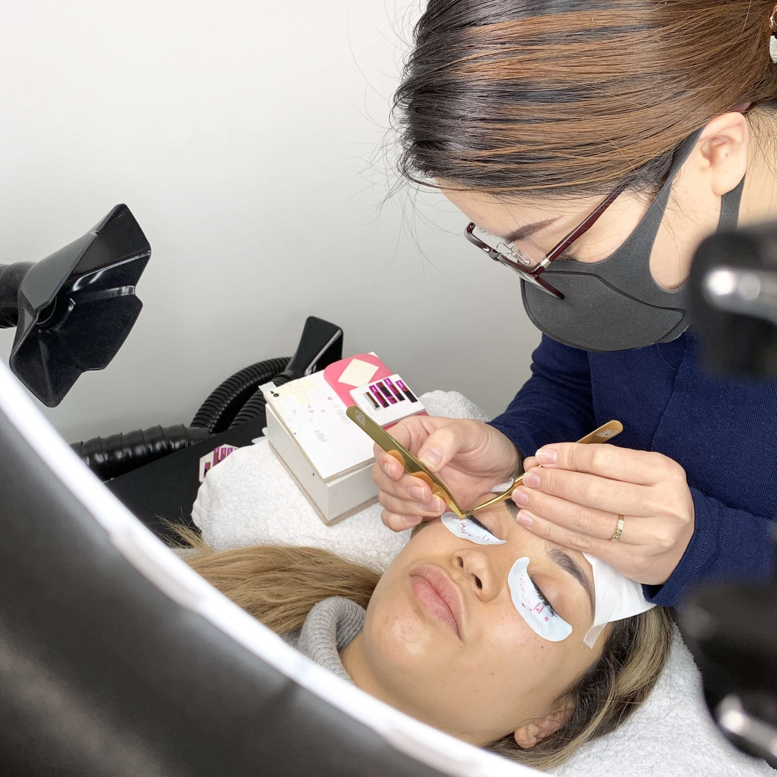Eyewonderlust Importance of Refilling Eyelash Extensions Blog - Eyelash Technician Working on Woman Client Eyelashes