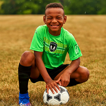 male soccer player kneeling with ball
