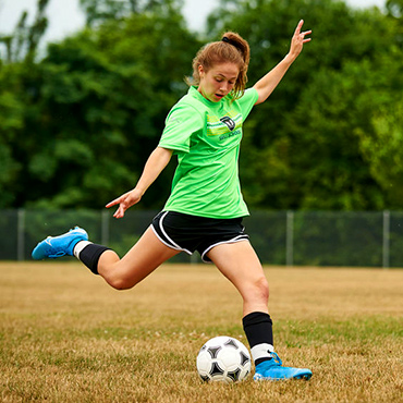 female soccer player winding up to kick ball