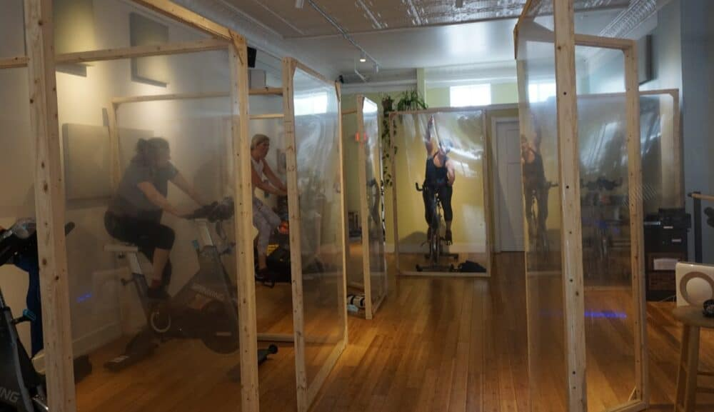 People on exercise bikes in plastic pods designed to stop the spread of COVID