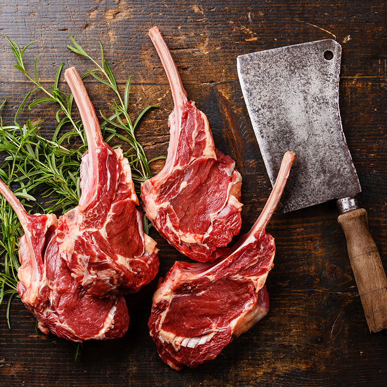 4 pieces of beef laying over herb with meat cleaver