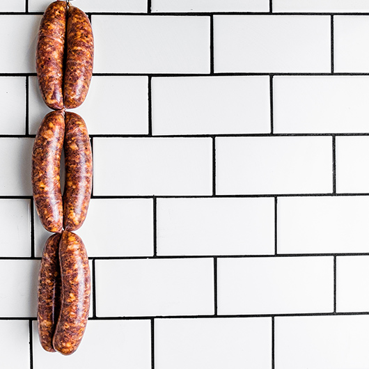 Six sausage links hanging in front of subway tile