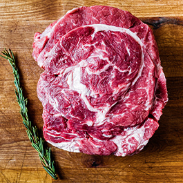 Large piece of beef on a wood board with a bright green swig of rosemary