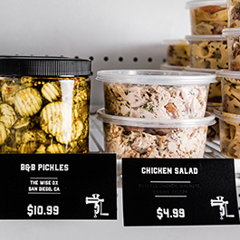 Jarred pickles and chicken salad in deli case