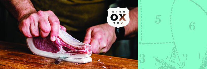 Hand cutting a piece of pork. Wise Ox logo