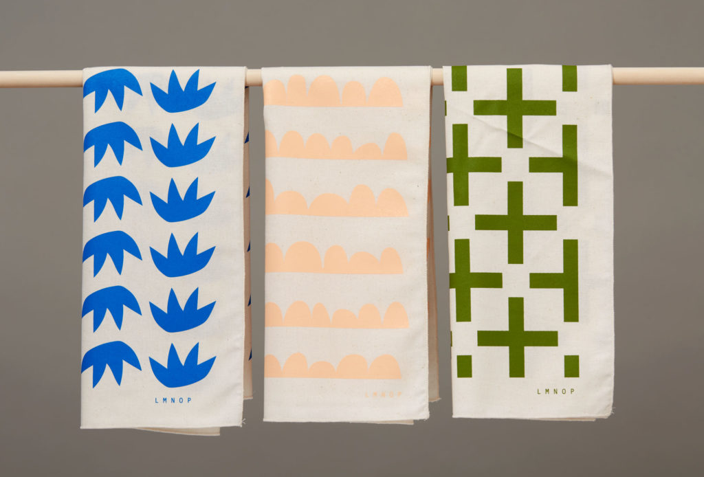 graphic tea towels hanging on a dowel
