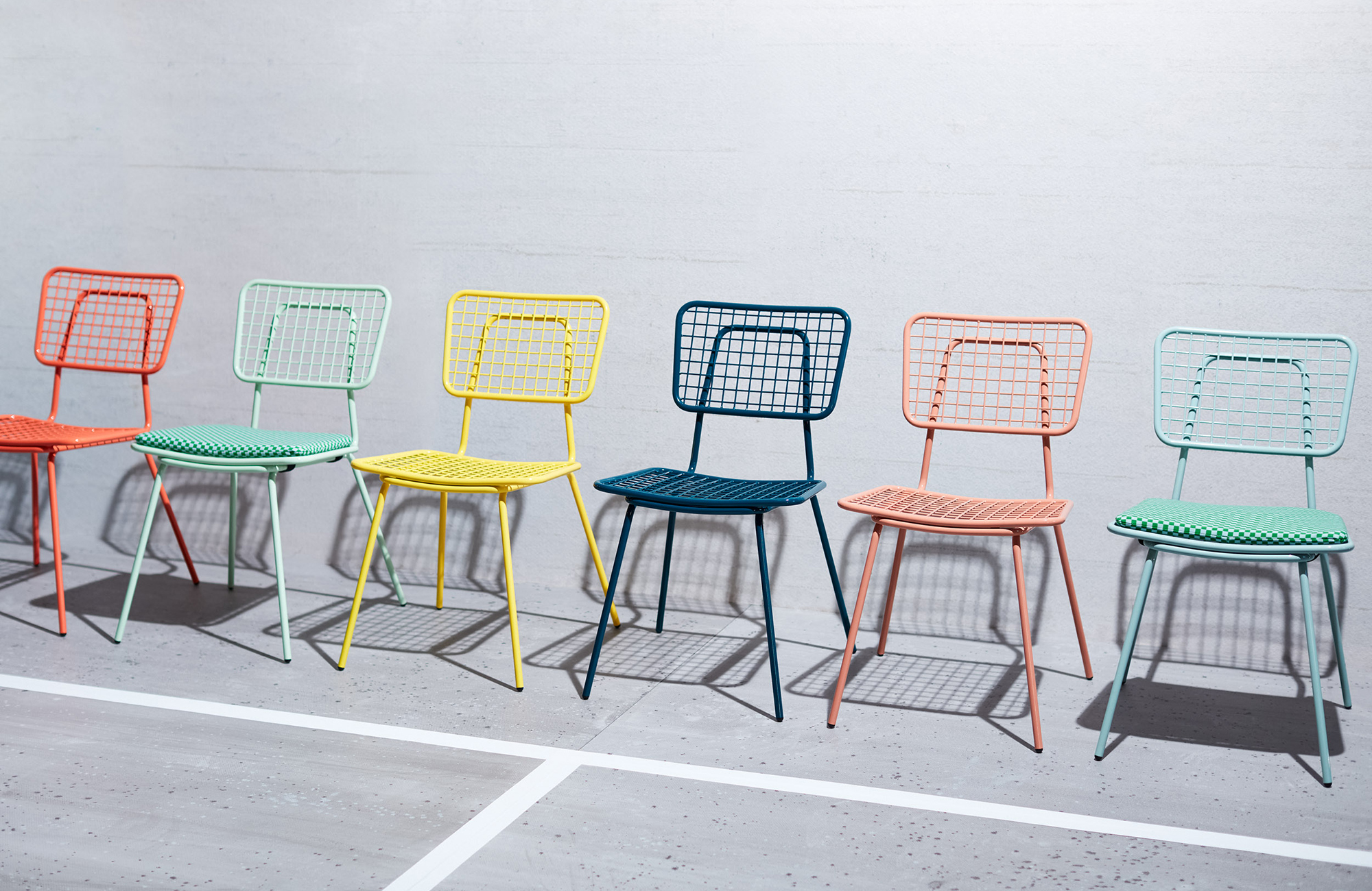 A row of metal wire chairs in different colors