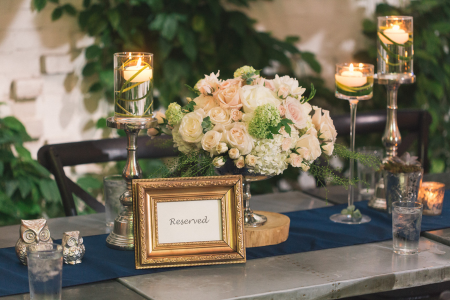 la-vie-en-rose-wedding-reception-ceremony-downtown-tampa-bay-invitation-bride-and-groom-floral-decor-centerpieces-books-gold-mercury-vase-roses-hydrangea-green-fern-spray-rose-candles-stems-ecclectic-succulent-votive-candles-birchwood-branch-moss-navy-table-runner-bridal-party-head-table-reserved-the-oxford-exchange