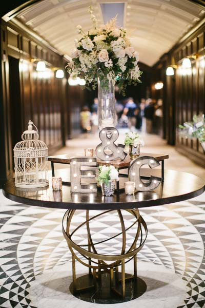 la-vie-en-rose-tampa-bay-Florida-wedding-love-ceremony-reception-letters-bird-cage-votives-table-bride-and-groom-initials-flowers-large-arrangement-greenery-white-blooms-blush-roses-stock-hydrangea-eucalyptus-astillbe-ivory-elegant-The-Oxford-Exchange