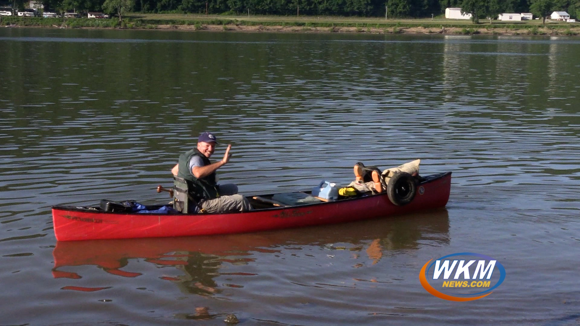 Man Canoeing in Coast to Coast Expedition Enjoys Local Riverfront