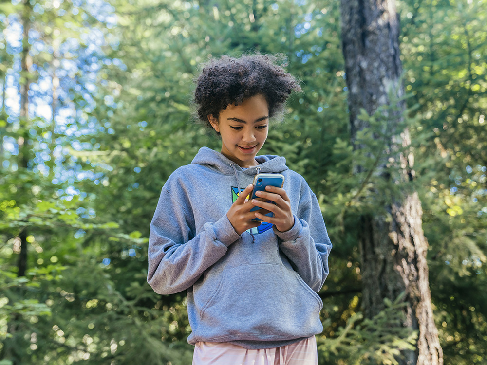 Teen looking at mobile phone in forest