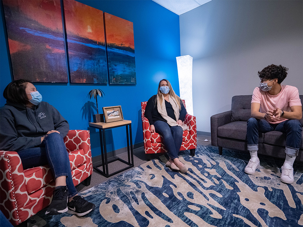 Counselor sitting with two clients
