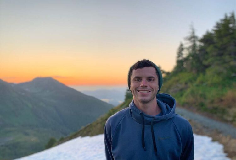 Young man standing on mountaintop at sunset