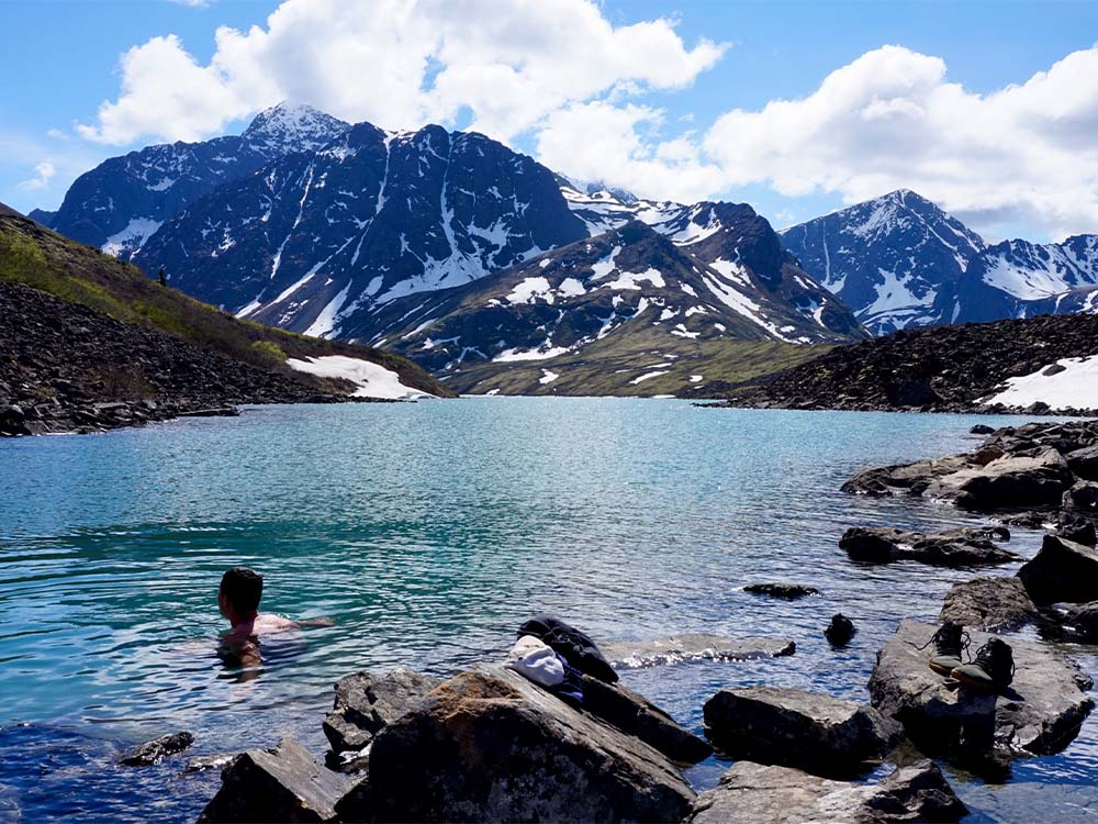 Person swimming in a mountain lake