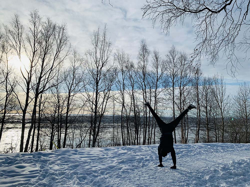 Person doing handstand on snowy trail.
