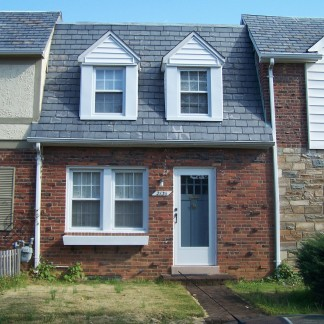 A brick house with a gray roof in Glebewood Village