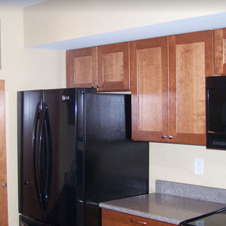 A kitchen with wooden cupboards and a black refrigerator