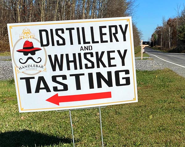 Yard Sign in grass that reads: Whiskey Tasting!