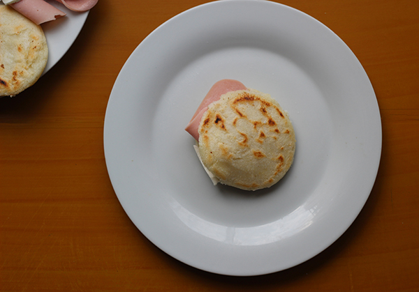 An Arepa stuffed with ham on a white plate