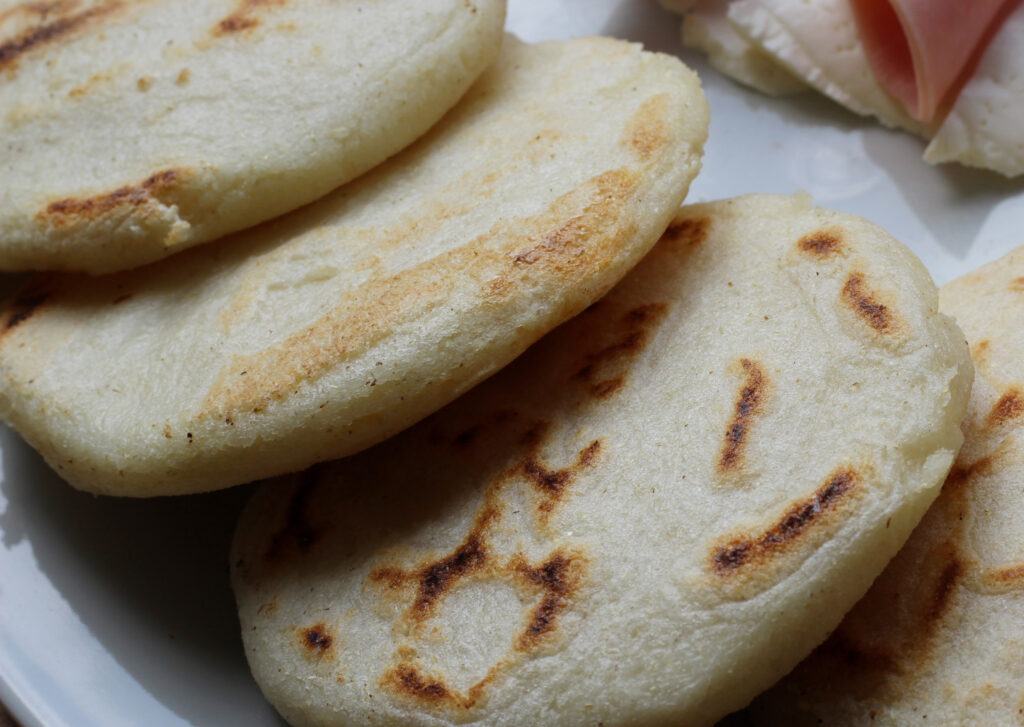 Arepas served with ham and cheese on a white plate