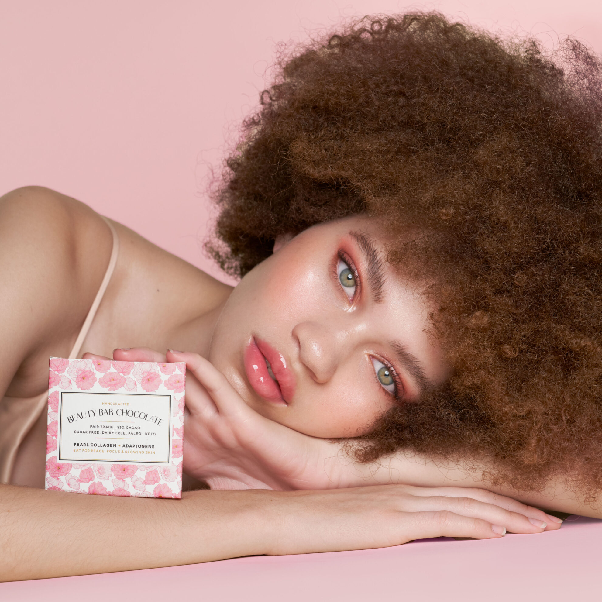 Beauty Bar Chocolate Image Nailed It Women laying on arm with pink chocolate box on pink backdrop