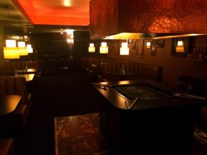 The communal grill, surrounded by plush booths.