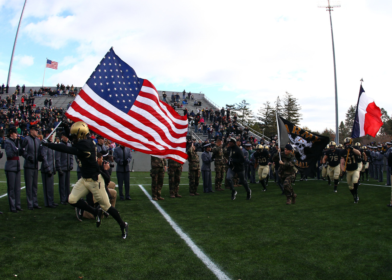 Nov 14, 2015; West Point, NY, USA; Army Black Knights defensive back Jared Rogers (18) carries an American flag on to the field alongside a cadet carrying a French flag before a game against Tulane at Michie Stadium. The tribute comes a day after terrorist attacks hit Paris, France. Mandatory Credit: Danny Wild-USA TODAY Sports
