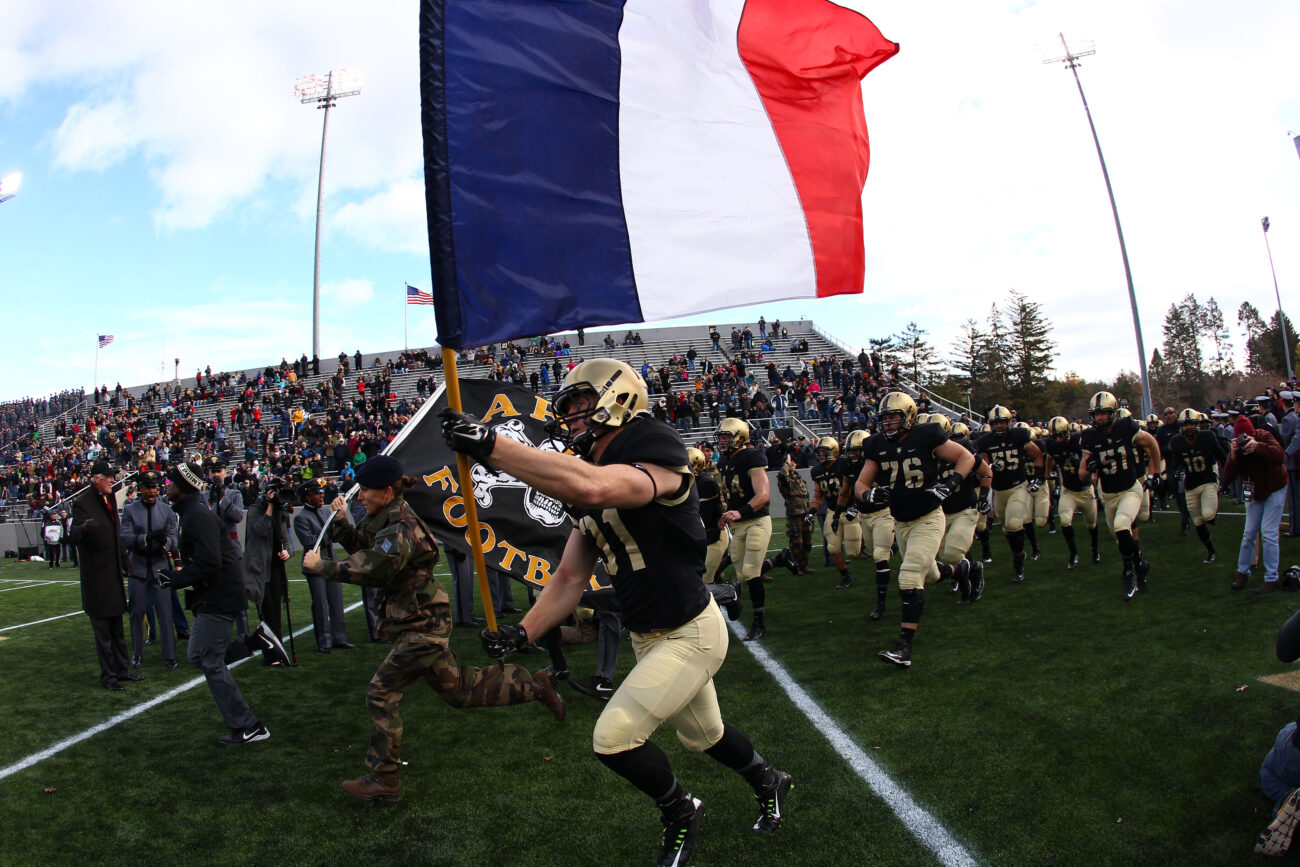 Nov 14, 2015; West Point, NY, USA; Army Black Knights defensive back Caleb McNeill (31) carries a French flag on to the field alongside a French exchange cadet before a game against the Tulane Green Wave at Michie Stadium. Army honored the French a day after terrorist attacks in Paris, France. Mandatory Credit: Danny Wild-USA TODAY Sports