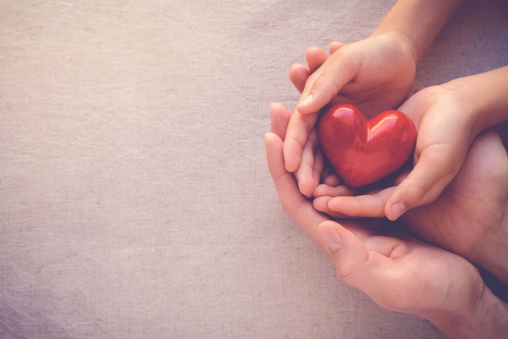 A child and adult cupping hands while holding a heart