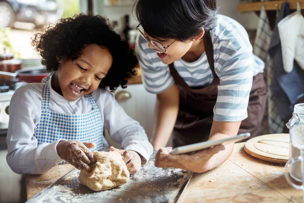 A woman teaches a little girl how to bake.