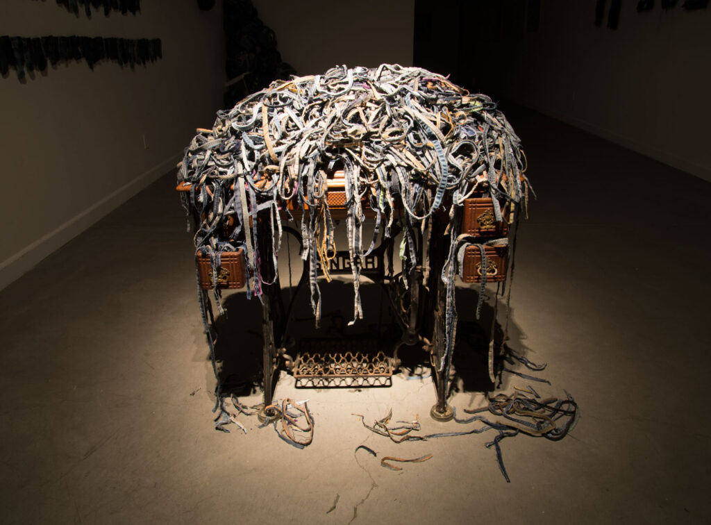 Apart at the Seams (2020) jean seams, Singer sewing machine and table $6500