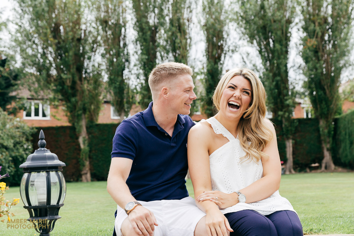 relaxed couples portrait sat in their garden by creative cotswold wedding photographer
