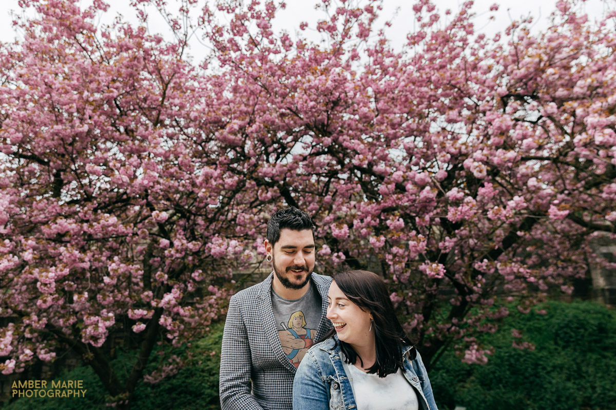 happy couple standing in front of pink blossom tree by best cotswold engagement photographer