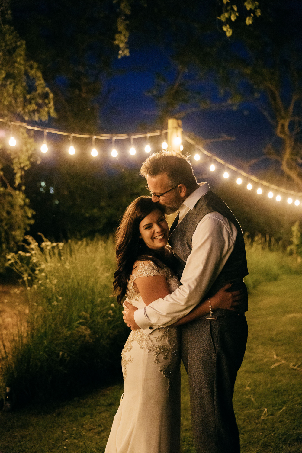 relaxed evening portraits under festoon lights by cotswold wedding photographer