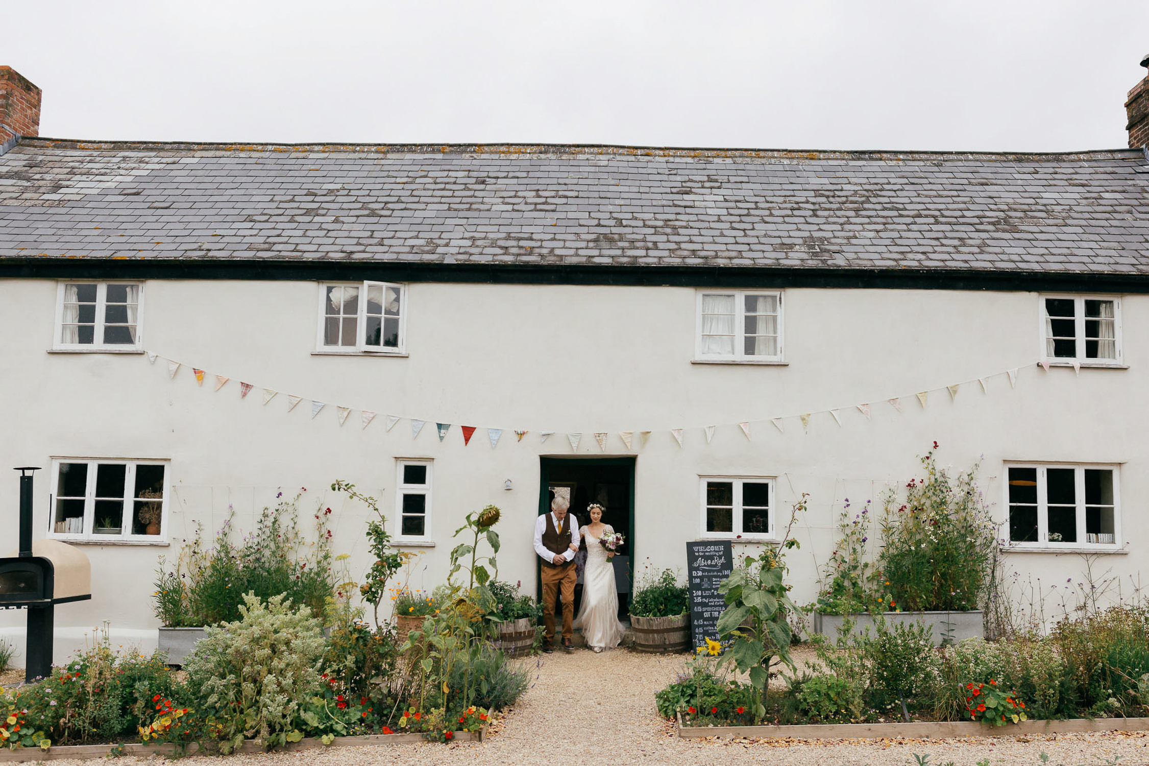 wide landscape view of bride and dad walking to outdoor ceremony at river cottage summer wedding
