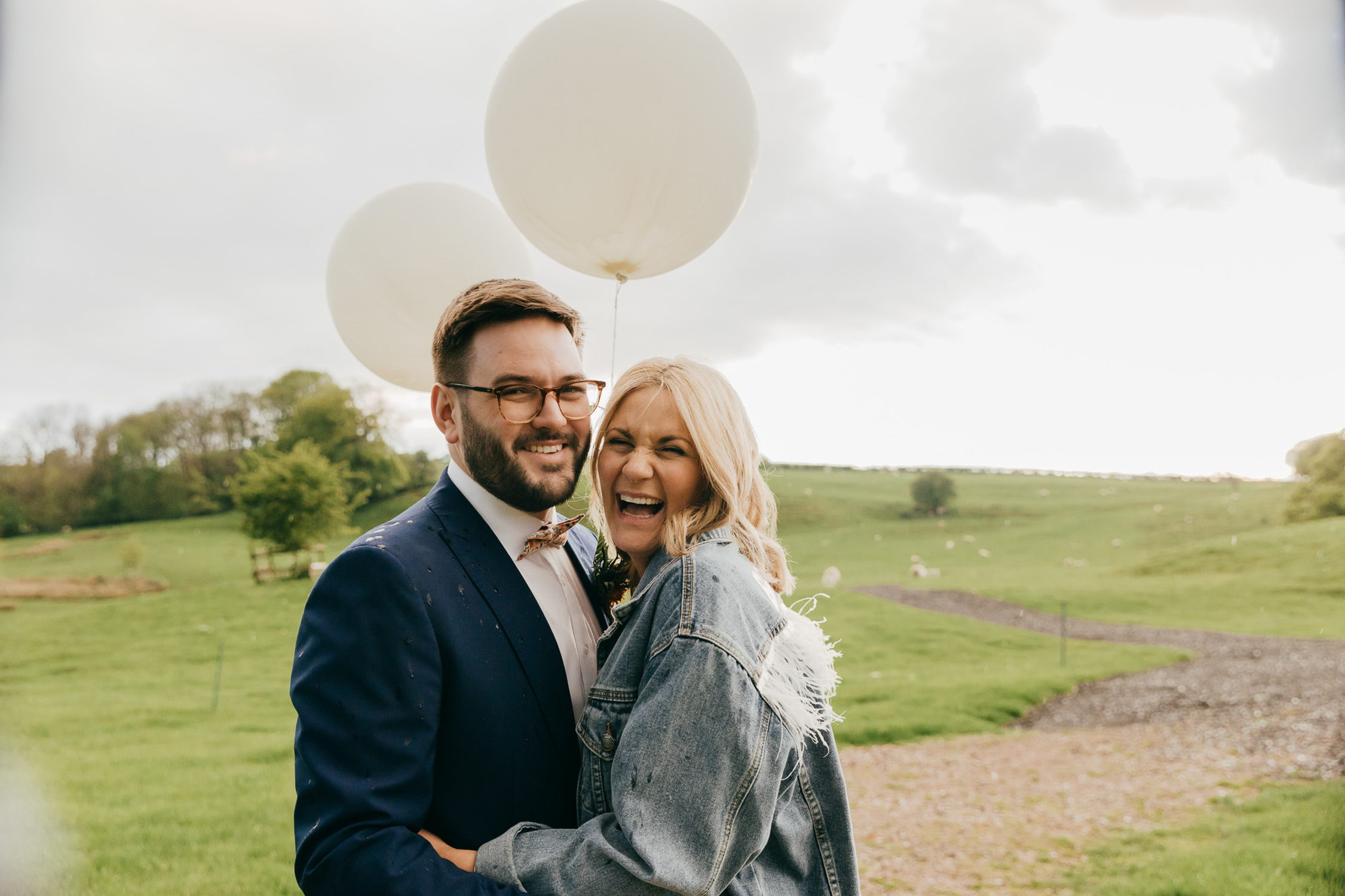 joyful portrait of bride and groom with balloons at kingscote barn in gloucestershire