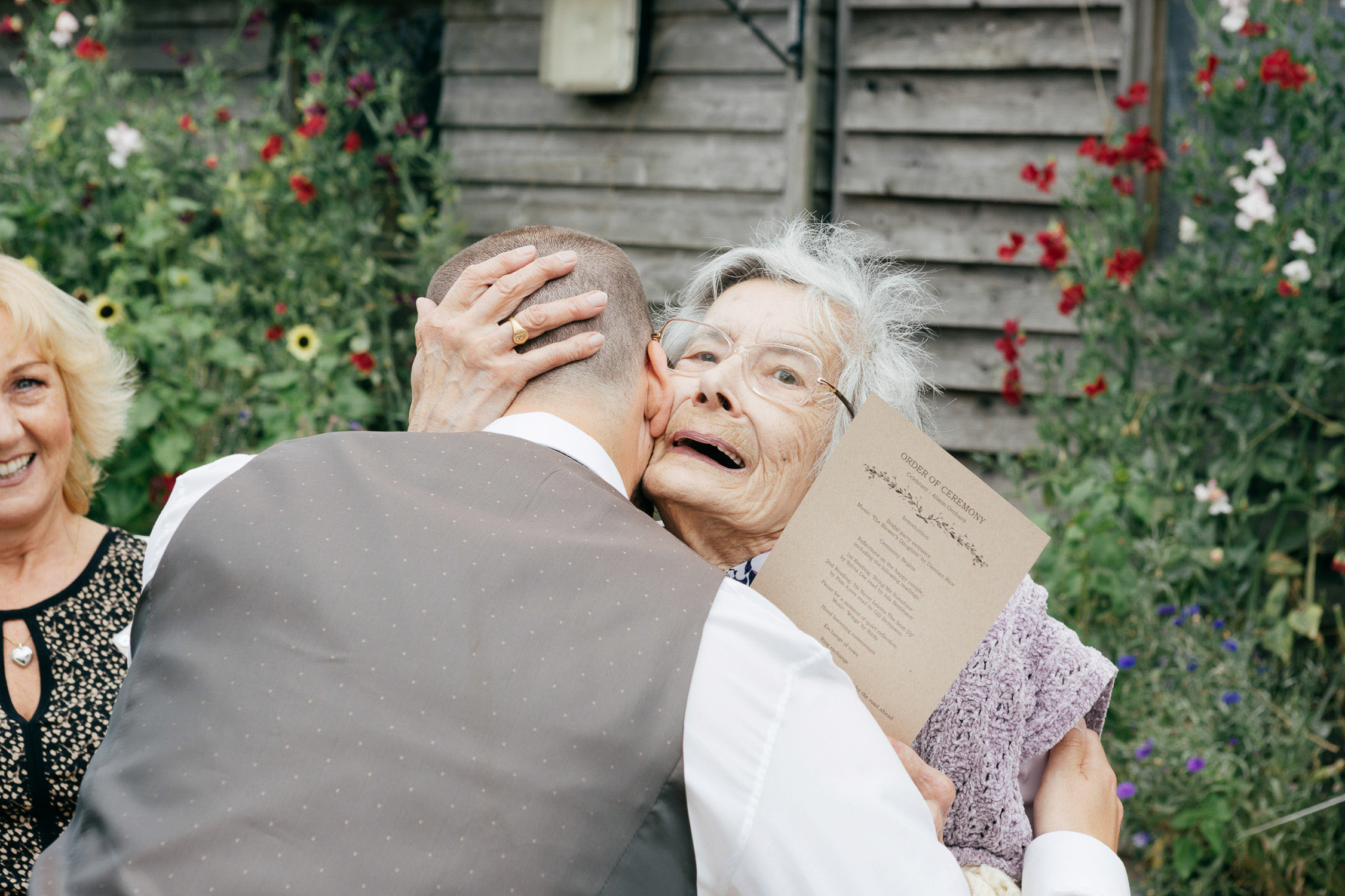 candid wedding photos of grandma hugging groom
