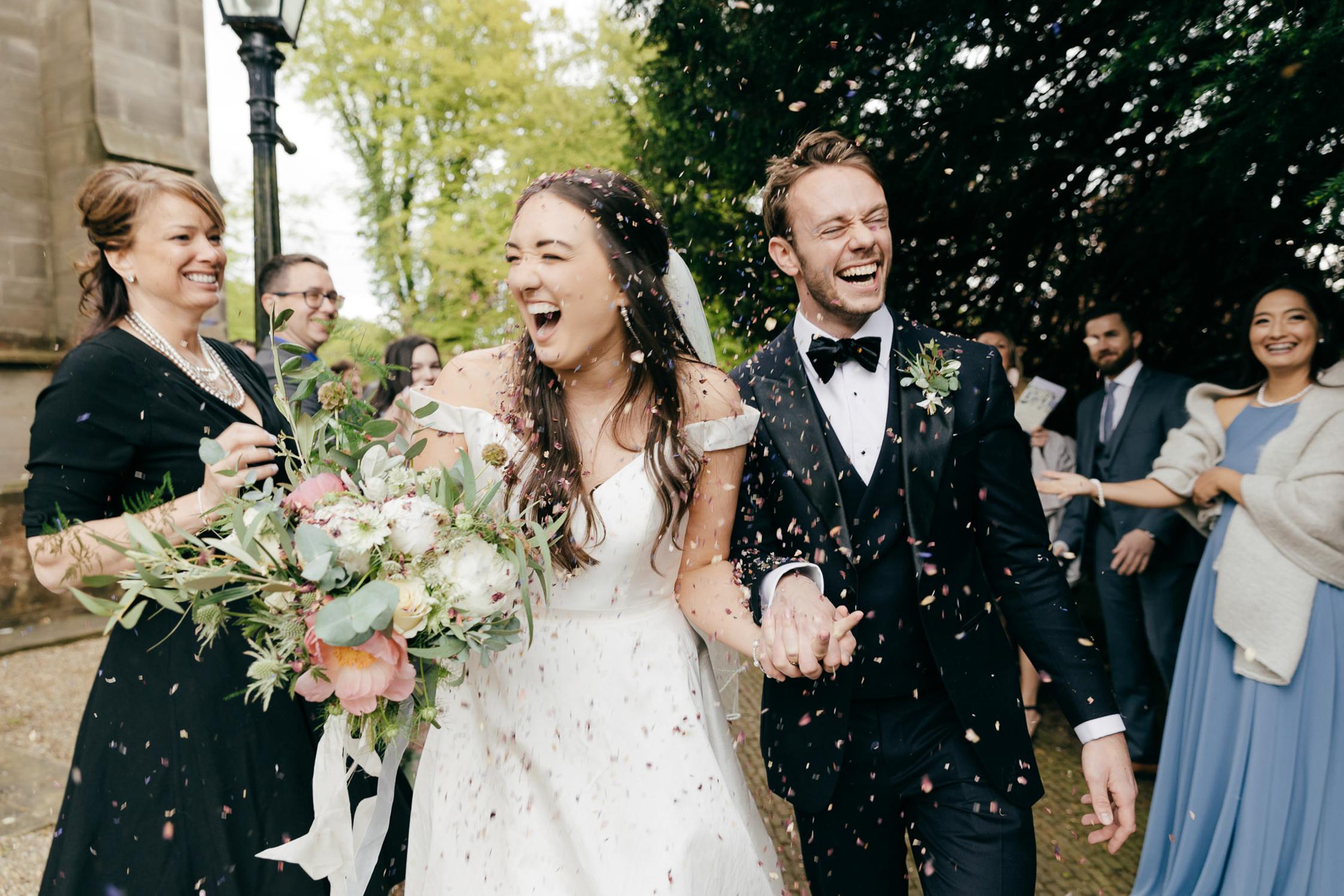Fun joyful and natural wedding photo of confetti throw outside church