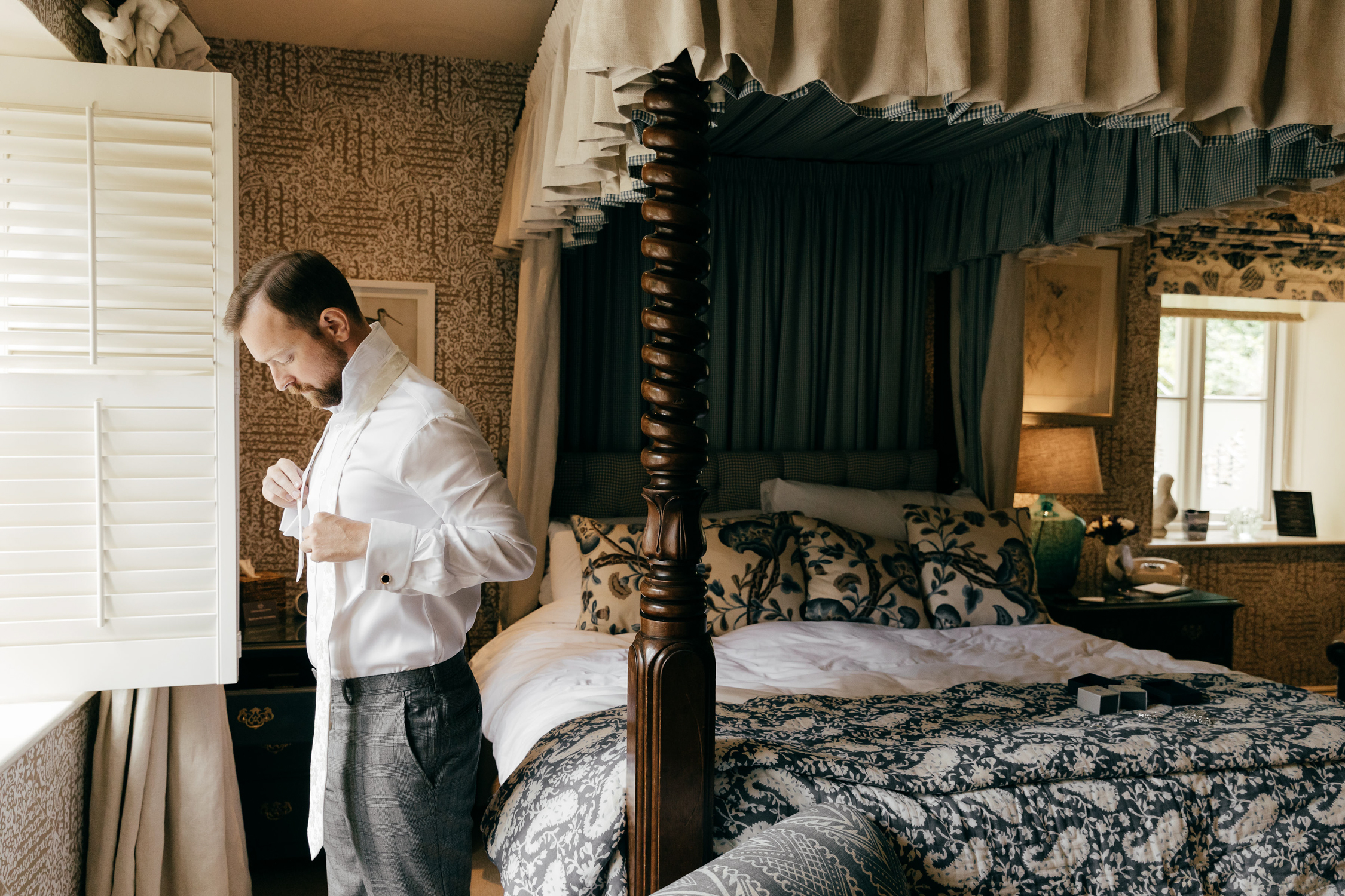 natural photo of groom getting ready at the swan hotel in bibury