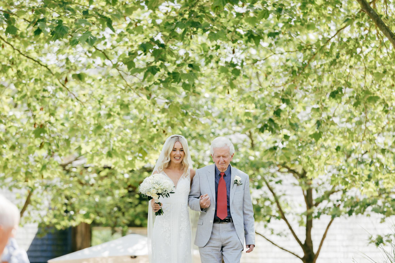 natural shot of bride arriving at outdoor wedding ceremony