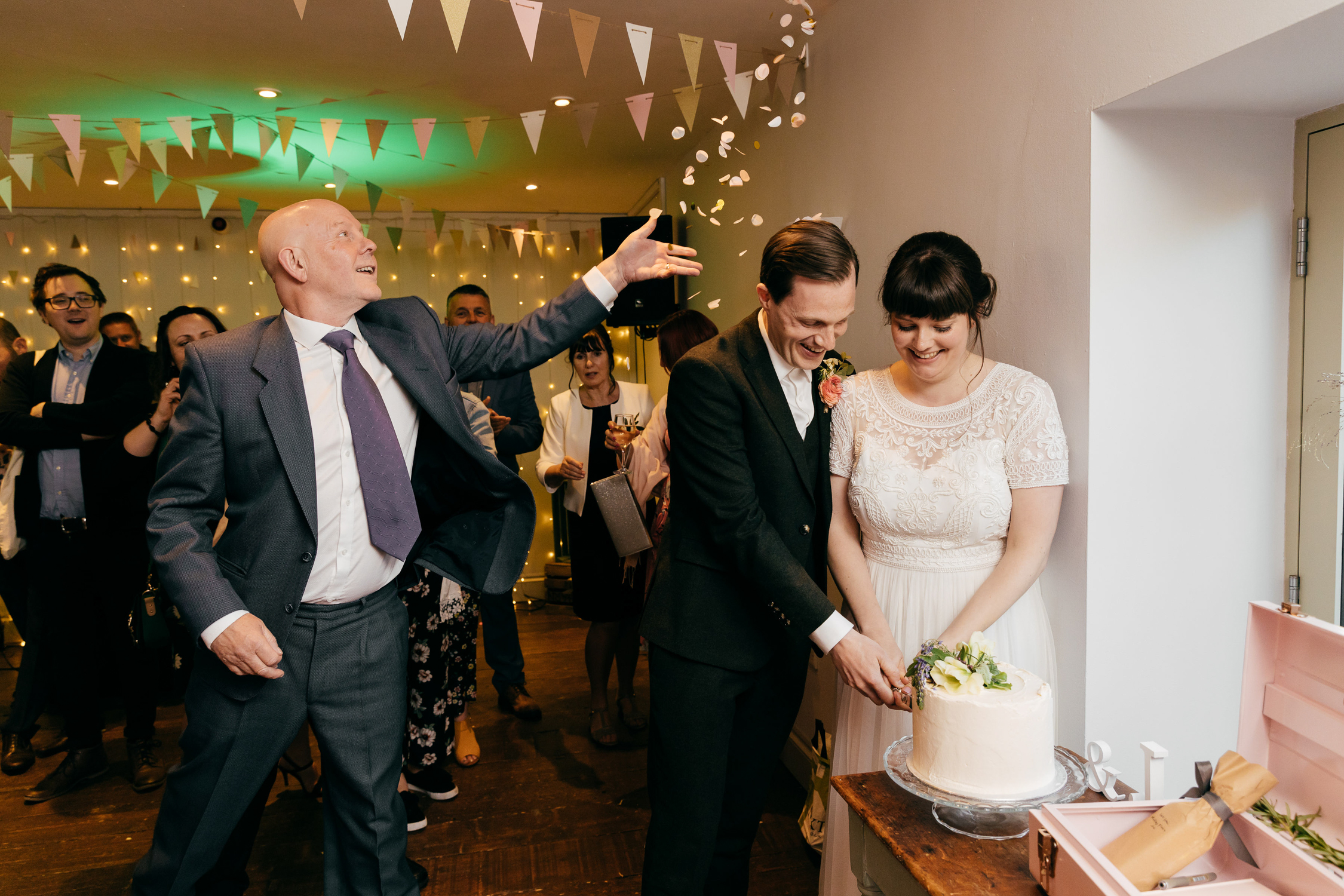 candid wedding photo of surprise confetti being thrown during the cake cut