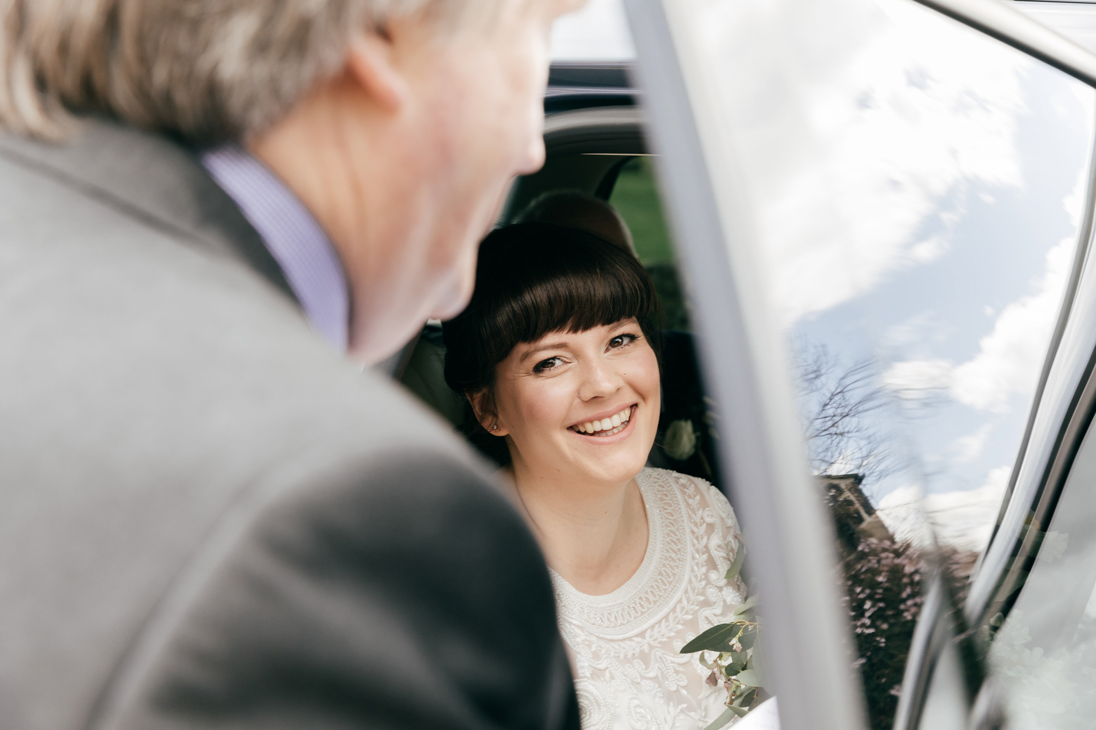 documentary wedding portrait of bride in car arriving at ceremony