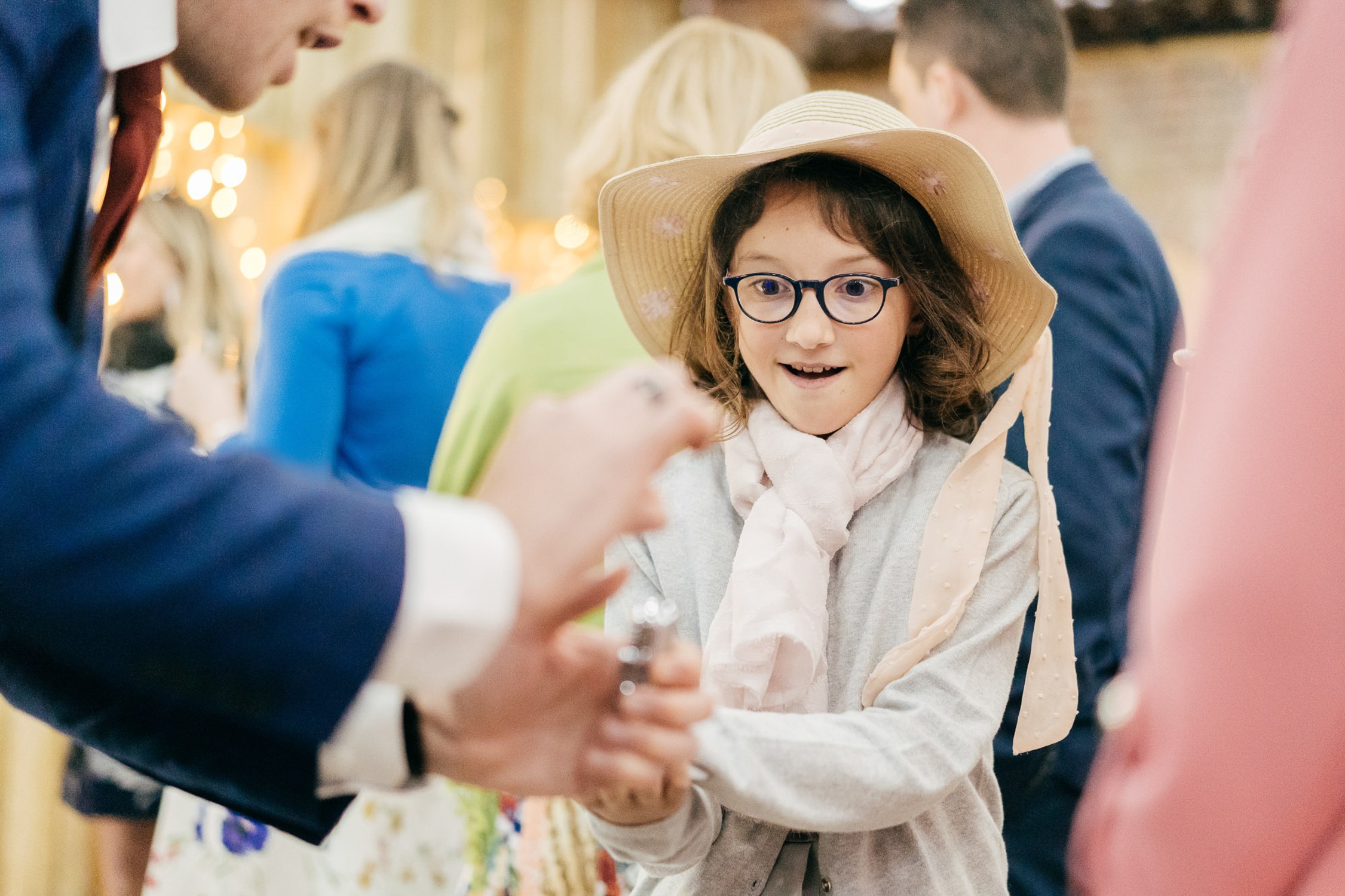 natural wedding photo of child's reaction to magic trick